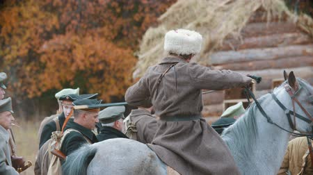 historical reconstruction : RUSSIA, REPUBLIC OF TATARSTAN 30-09-2019: A reconstruction of military operations in Russia in 1917 - an area surrounded by soldiers - a man standing on the horse and going forward
