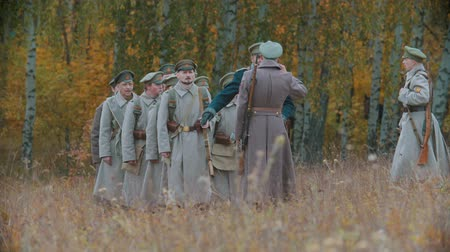 velitel : RUSSIA, REPUBLIC OF TATARSTAN 30-09-2019: A reconstruction of military operations in Russia in 1917 - Soldiers standing in the row and listening to their commander - salute gesture