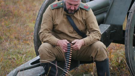 historical reconstruction : RUSSIA, REPUBLIC OF TATARSTAN 30-09-2019: A reconstruction of military operations in Russia in 1917 - A man soldier prepares the ammunition for charging in the machine gun