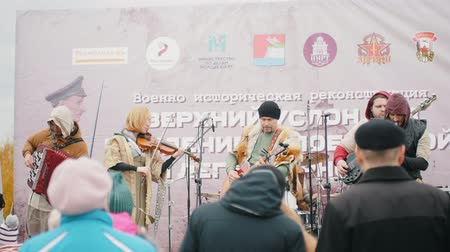 fuvolák : RUSSIA, REPUBLIC OF TATARSTAN 30-09-2019: A reconstruction of military operations in Russia in 1917 - A music band playing on stage on the festival outdoors - a man playing flute and another singing in the microphone