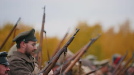 historical reconstruction : RUSSIA, REPUBLIC OF TATARSTAN 30-09-2019: A reconstruction of military operations in Russia in 1917 - Soldiers standing in the row and putting their guns up and down