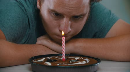 borrifar : A man is looking at a candle on the cake