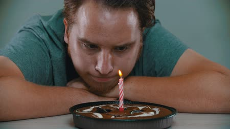 tatlı çörek : Sad man is trying to blow out the candle on the cake
