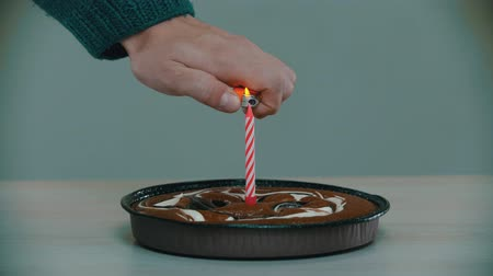 muffin : Lighting a pink candle on a cake with a lighter