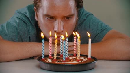 muffin : Sad man is blowing out the candles on the birthday cake Stock Footage