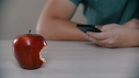 érintőképernyő : A man is looking at the phone next to a bitten apple
