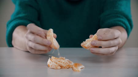 rind : A man is breaking in pieces a ripe orange on the table Stock Footage