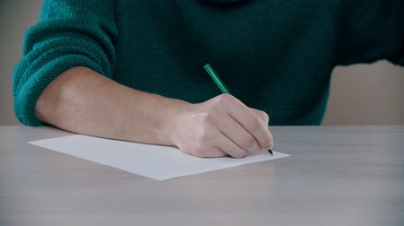kciuk : A man is actively writing word on a paper Wideo