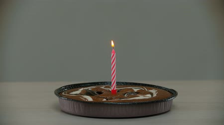 muffin : A lonely cake with candle is standing on the table Stock Footage