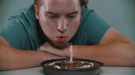 muffin : A man is blowing out a candle on a birthday cake