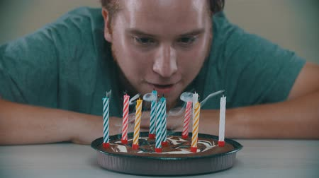 muffin : Man is blowing out the candles on the cake Stock Footage
