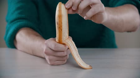 banan : A man is peeling a ripe banana