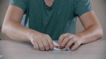 сложены : Man is folding a white paper airplane on the table Стоковые видеозаписи