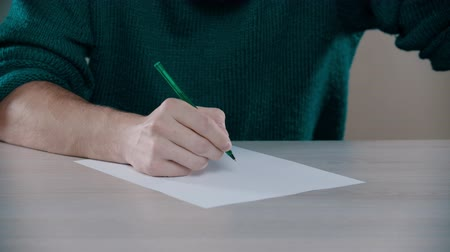 írott : A man is going to write words down on the table Stock mozgókép