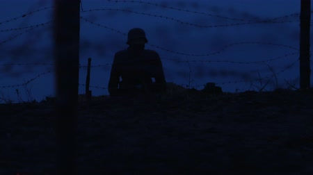 戦闘 : A soldier sitting in the trench at night on the patrol 動画素材