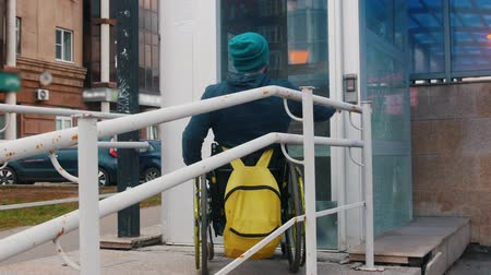 bağımlı : Disabled man in wheelchair entering special elevator for disabled people