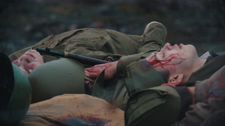 歩兵 : 19-10-2019 RUSSIA, REPUBLIC OF TATARSTAN: a lot of wounded soldiers covered in blood lying on the scorched ground of the forest - backstage of filming military movie