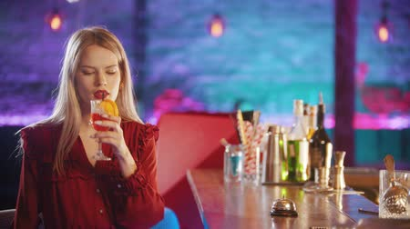 губная помада : Gorgeous blonde young woman with red lipstick sitting by the bartender stand - drinking a red beverage from the straw