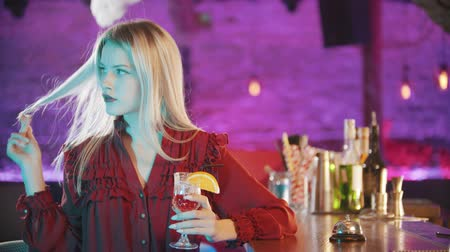 verres à vin : Gorgeous blonde young woman with red lipstick sitting by the bartender stand and playing with her hair and holding a drink - neon blue lighting