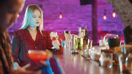 saman : Gorgeous blonde young woman sitting by the bartender stand - drinking a beverage from the straw - a man sitting in his phone on the foreground