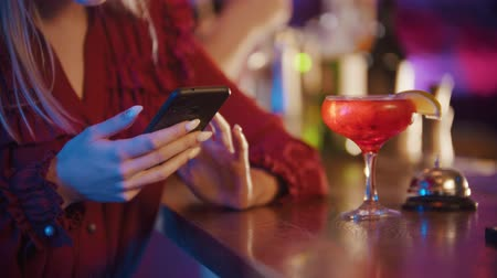 jazz : Young woman sitting by the bartender stand and using her phone Stock Footage