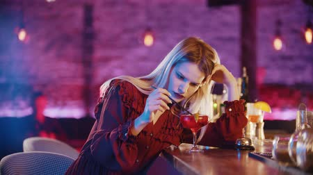 saman : Gorgeous bored young woman sitting by the bartender stand and stirs the drink with a straw