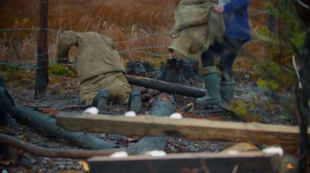 bojiště : Backstage of filming - Dead soldier lying on the iron wire - piece of log on a foreground - People walking around