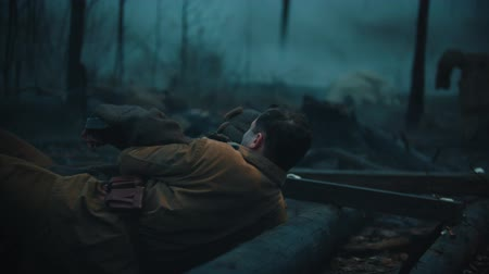 combate : Wounded soldiers crawl on the ground in the misty forest - one soldier rescues his comrade
