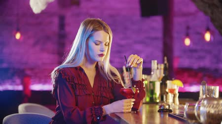 boring : Bored young blonde woman sitting by the bartender stand and stirs the drink with a straw Stock Footage