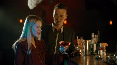 дата : A man meeting a girl in the bar - standing by the stand and talking with young woman - drinking cocktails