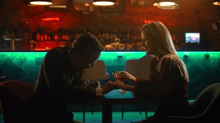 дата : A spectacular couple having a date in the bar - a man holding womans hand and talking to her