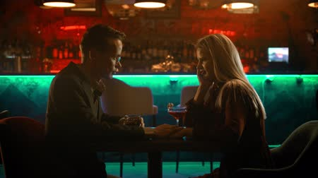 дата : A bewitching couple having a date in the bar - a man holding womans hand and making her shy