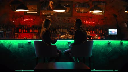дата : A bewitching couple having a date in the bar - sitting by stand and laughing Стоковые видеозаписи