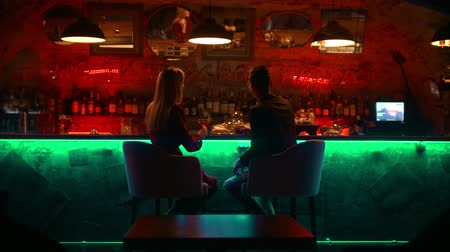 дата : A bewitching couple having a date in the bar - sitting by stand and having a talk
