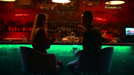 дата : A bewitching couple having a date in the bar - sitting by stand and clinking their glasses - cheers Стоковые видеозаписи