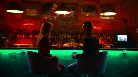 дата : An attractive couple having a date in the bar - sitting by stand and clinking their glasses - cheers