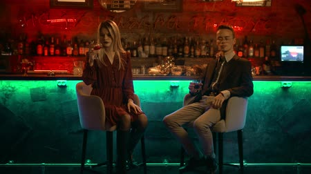 паб : A couple having a date in the bar - sitting on the bar chairs towards the camera and drinking their beverages