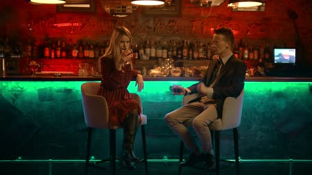 дата : A couple having a date in the bar - sitting on the bar chairs towards the camera - drinking their beverages and talking about something Стоковые видеозаписи