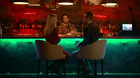 дата : A bewitching couple having a date in the bar - bartender standing and rubs the glass and talking with a couple Стоковые видеозаписи