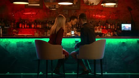 cheers : A bewitching couple having a date in the bar - bartender doing his job and the couple looking at the pictures in the phone
