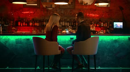 дата : A bewitching couple having a date in the bar - sitting by the stand and looking at the pictures in the phone