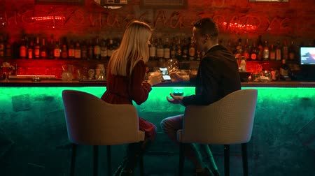 дата : A young couple having a date in the bar - sitting by the stand and looking at the pictures in the phone