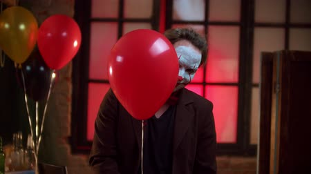 diabeł : A scary clown slightly peeking out from the red balloon and creepy smiling