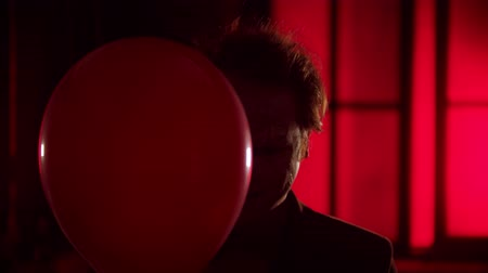 uğursuz : A scary clown peeking out from the red balloon and creepy smiling - flashing blinking light