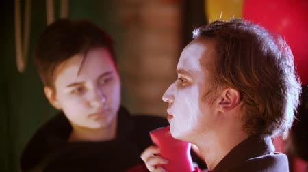 diabeł : Make-up artist applying paint on the man clown in the dressing room