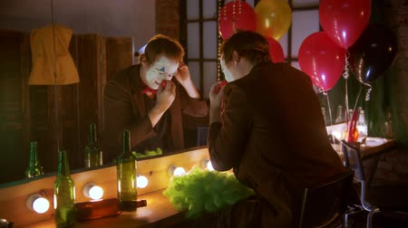 diabeł : A man clown putting on a red nose - sitting in front of the mirror and smile