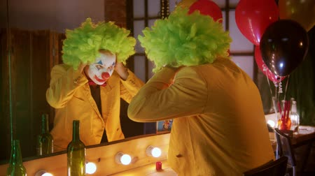 peruka : A man clown put on a green wig and smiling to the mirror Wideo