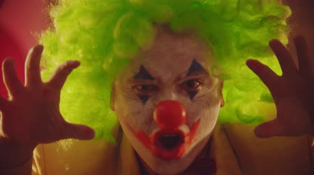 peruka : A crazy man clown closing his face with his hands and showing creepy emotions and actions