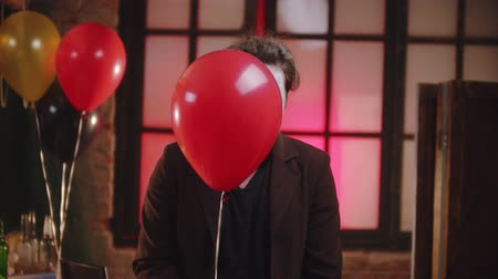 uğursuz : A scary clown peeking out from the red balloon and creepy smiling Stok Video