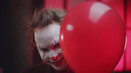diabeł : A scary clown with cracked paint on the face peeking out from the red balloon and creepy smiling